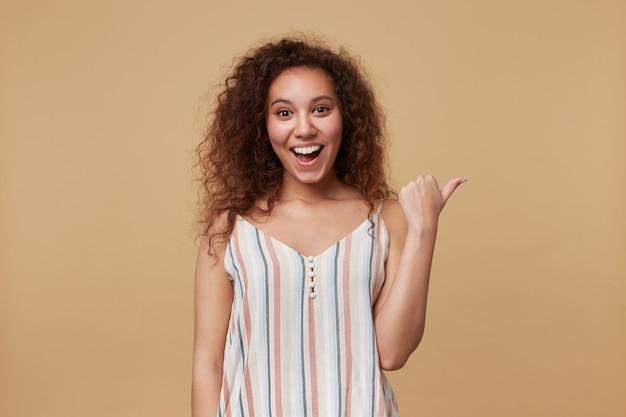 Ritratto di giovane gioiosa donna riccia dai capelli castani che ride felicemente mentre indica da parte con il pollice, isolato su beige in estate a strisce in alto