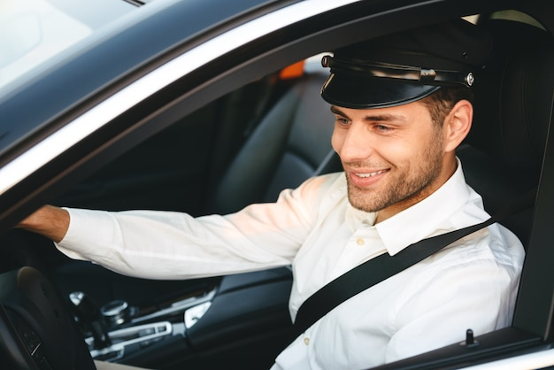 Portrait of young joyful man taxi driver in uniform and cap, driving car wearing seat belt