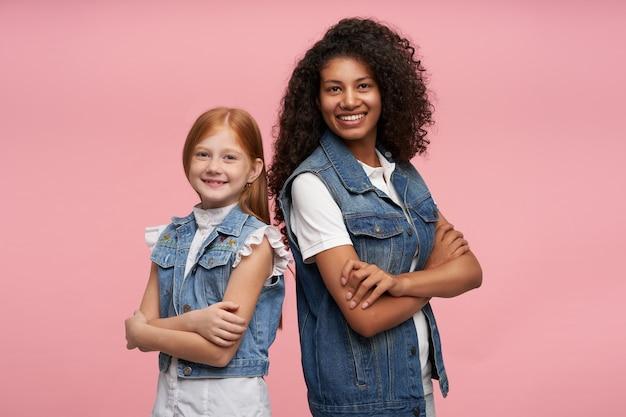 Ritratto di giovani ragazze adorabili gioiose che tengono le mani giunte e che guardano allegramente, essendo di ottimo spirito e mostrando le loro piacevoli emozioni sul rosa