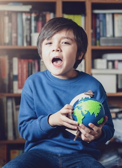 Portrait young kid happy face holding globe sitting at library, child boy learning about geography, education and homeschooling concept