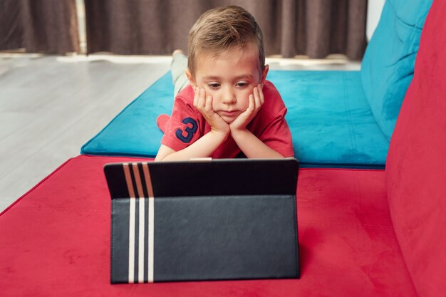 Portrait of a young kid at home watching cartoon on the laptop.