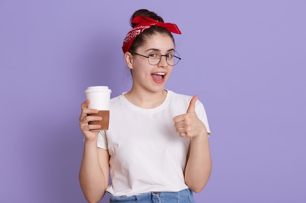 Portrait of young lady in casual white t shirt standing with cup of coffee to go isolated over lilac space. pretty girl happily showing thumb up gesture while  and winks.