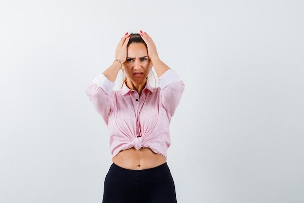 Ritratto di giovane donna stringendo la testa con le mani in camicia, pantaloni e guardando triste vista frontale