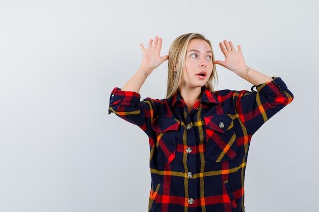 Ritratto di giovane donna che fa un gesto divertente in camicia a quadri e guardando perplesso vista frontale
