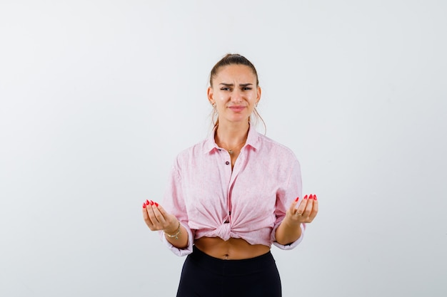 Ritratto di giovane donna che fa il gesto italiano, scontento della domanda stupida in camicia, pantaloni e guardando la vista frontale infastidita