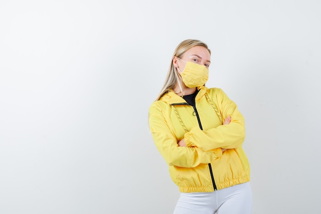 Portrait of young lady holding arms folded in jacket, pants, mask and looking proud front view
