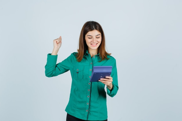 Portrait of young lady holding calculator, showing winner gesture in green shirt and looking blissful front view