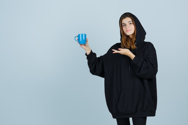 Portrait of young lady holding cup while pretending to show something in oversized hoodie, pants and looking confident front view