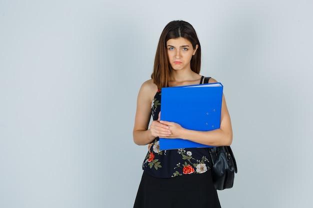 Ritratto di giovane donna che tiene cartella in camicetta, gonna e guarda cupa vista frontale