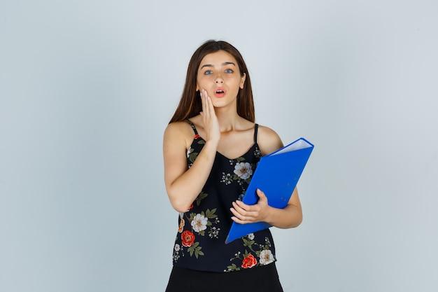Ritratto di giovane donna che tiene la cartella, tenendo la mano sulla guancia in camicetta, gonna e guardando la vista frontale meravigliata