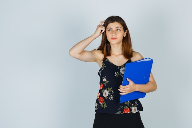 Ritratto di giovane donna che tiene la cartella mentre si gratta la testa in camicetta, gonna e guarda indecisa vista frontale