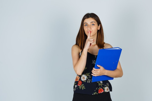 Ritratto di giovane donna che tiene in mano una cartella mentre mostra il gesto del silenzio in camicetta, gonna e guarda con attenzione la vista frontale