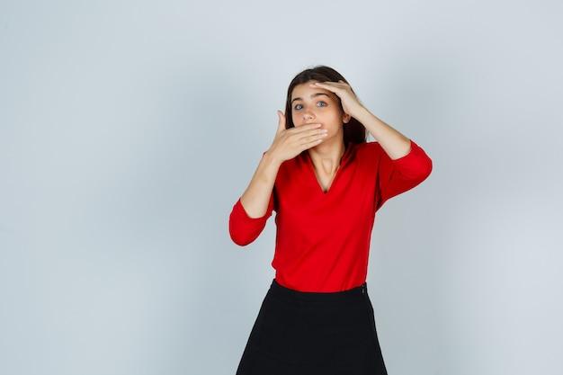 Ritratto di giovane donna che tiene la mano sulla bocca in camicetta rossa