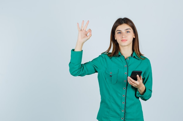 Portrait of young lady holding mobile phone, showing ok gesture in green shirt and looking pleased front view