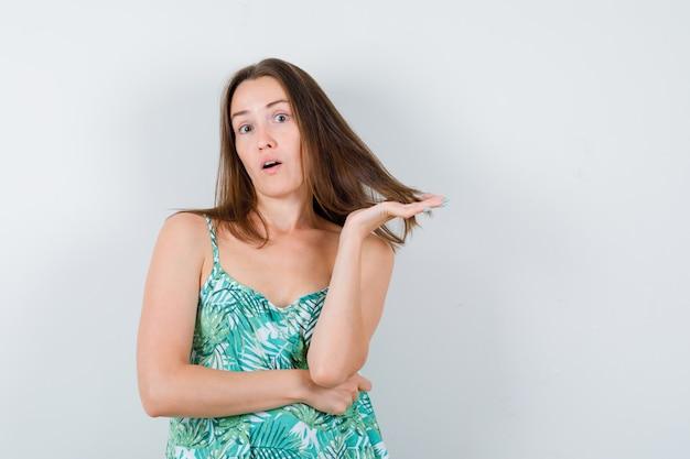 Ritratto di giovane donna che tiene una ciocca di capelli in camicetta e guarda perplessa vista frontale