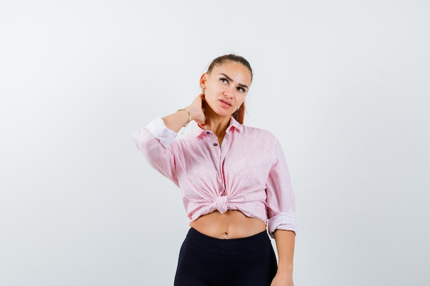 Portrait of young lady keeping hand on neck in shirt, pants and looking pensive front view