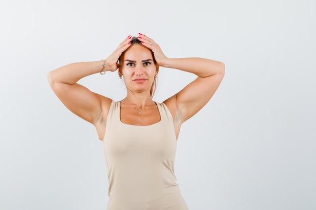 Ritratto di giovane donna tenendo le mani sulla testa in canottiera e guardando sconcertato vista frontale