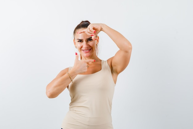 Portrait of young lady making frame gesture in tank top and looking cheery front view