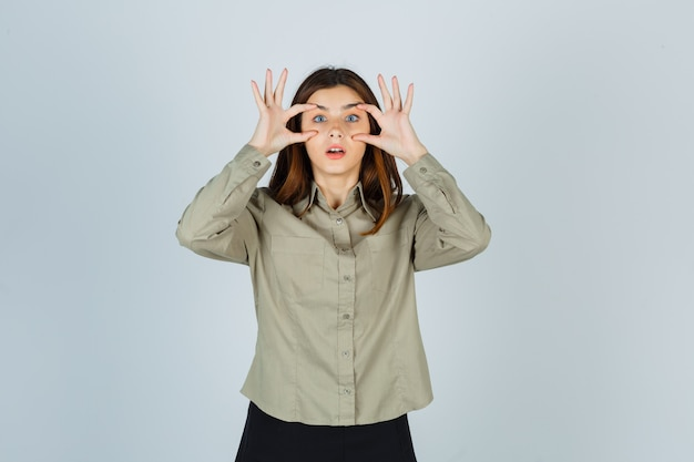 Portrait of young lady opening eyes with fingers in shirt, skirt and looking shocked front view
