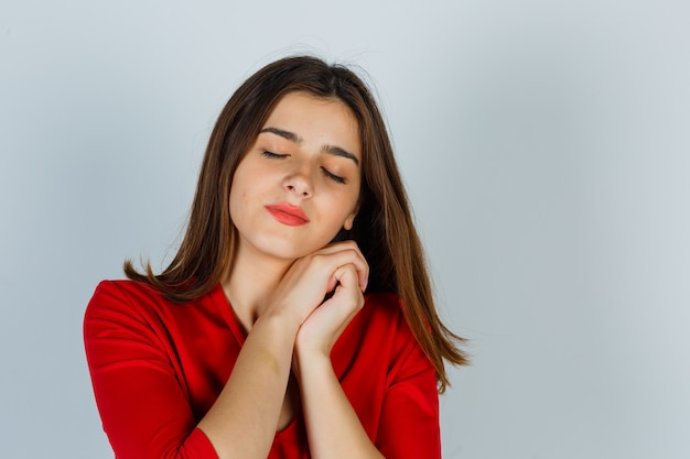 Portrait of young lady pillowing face on her hands in red blouse and looking sleepy