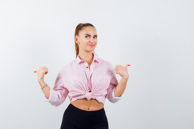 Ritratto di giovane donna che punta indietro con i pollici in camicia, pantaloni e guardando curioso vista frontale