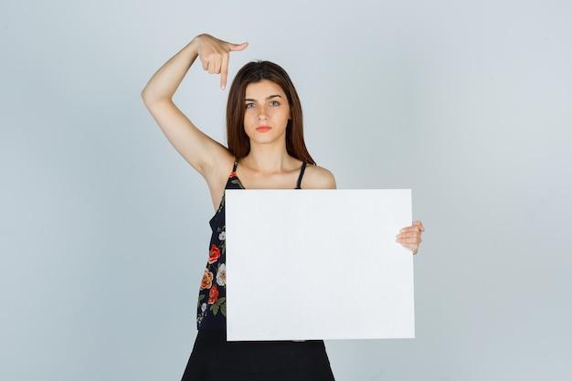 Ritratto di giovane donna che indica una tela bianca in camicetta, gonna e guarda seria vista frontale