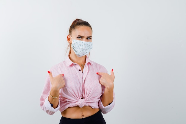 Portrait of young lady pointing at herself in shirt, mask and looking confused front view