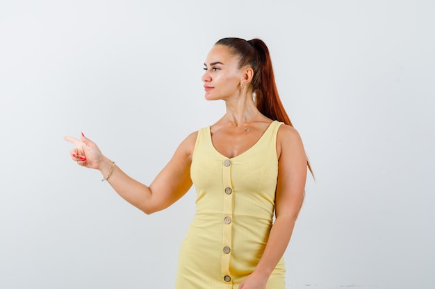 Portrait of young lady pointing left, looking aside in yellow dress and looking focused front view