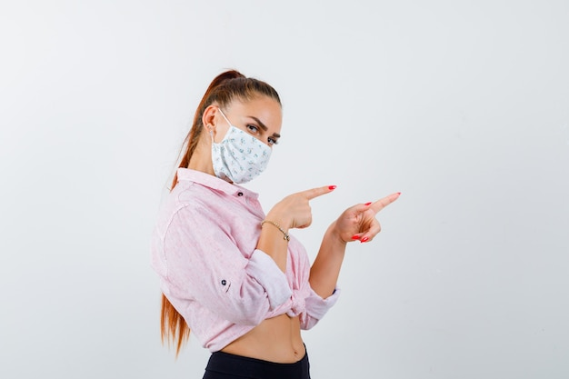 Portrait of young lady pointing right in shirt, mask and looking confident front view