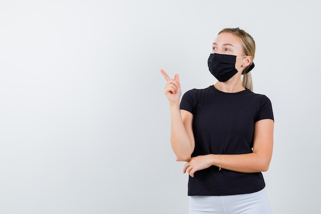 Portrait of young lady pointing at upper left corner in t-shirt, pants, medical mask