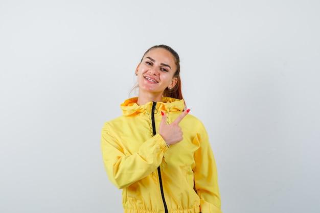 Ritratto di giovane donna che punta all'angolo in alto a destra in giacca gialla e guarda una vista frontale allegra