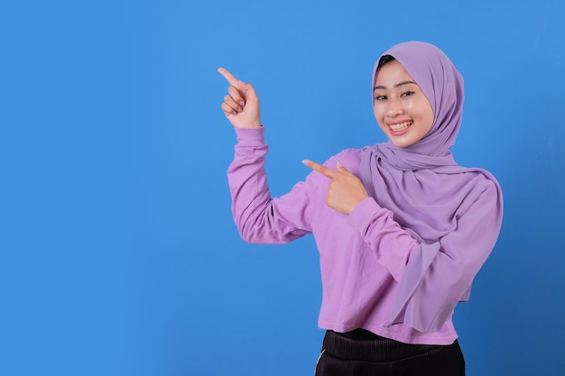 Portrait young lady pointing with two hands something using soft t shirt