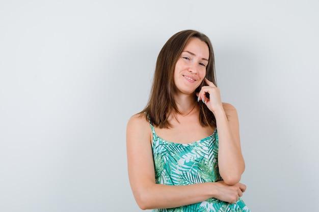 Ritratto di giovane donna in posa in piedi in camicetta e guardando affascinante vista frontale