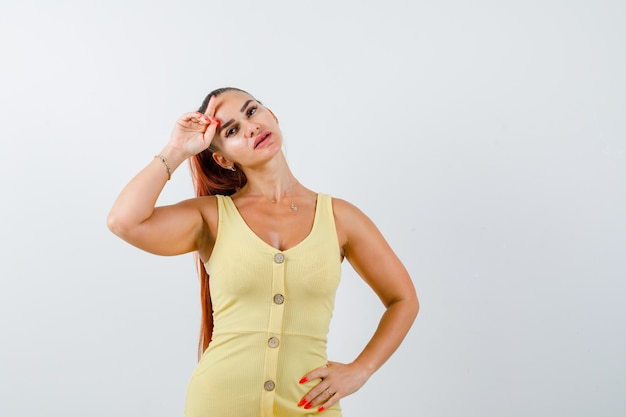 Portrait of young lady posing with hand on forehead in yellow dress and looking gorgeous front view