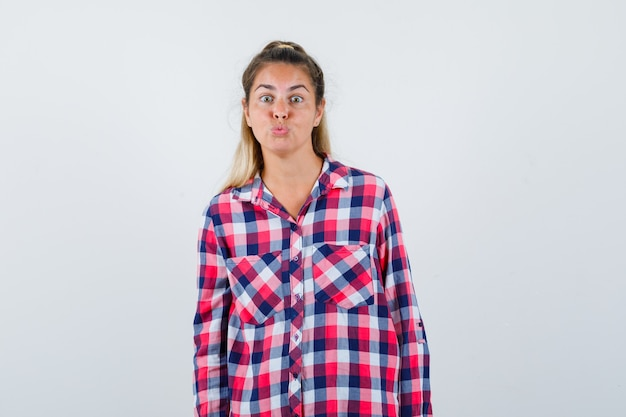Portrait of young lady pouting lips in checked shirt and looking lovely front view