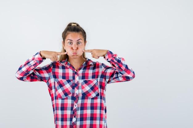 Ritratto di giovane donna premendo le dita sulle guance soffiate in camicia a quadri e guardando divertente vista frontale