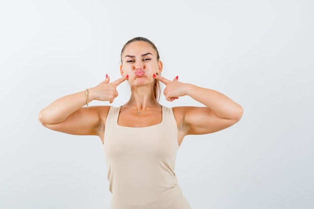 Portrait of young lady pressing fingers on puffy cheeks in tank top and looking funny front view