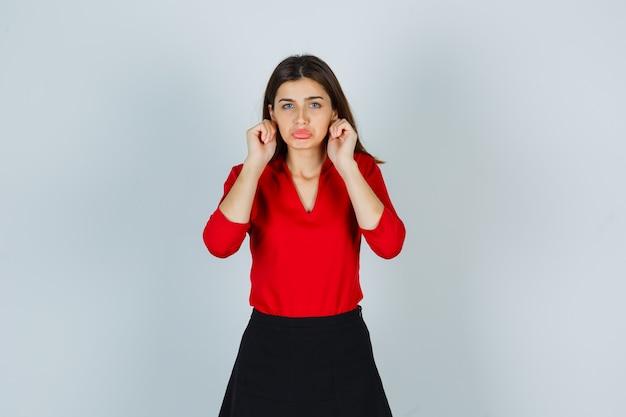 Ritratto di giovane donna che tira i lobi delle orecchie in camicetta rossa, gonna e sguardo offeso