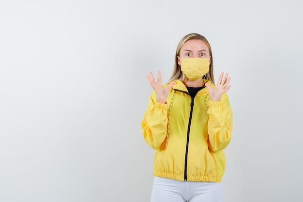 Ritratto di giovane donna che alza le mani per difendersi in giacca, pantaloni, maschera e vista frontale spaventata