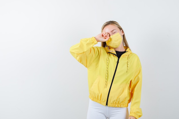 Portrait of young lady rubbing eye in jacket, pants, mask and looking sleepy front view