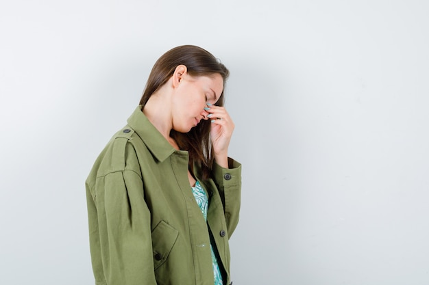 Portrait of young lady rubbing nose and eyes in green jacket and looking fatigued front view