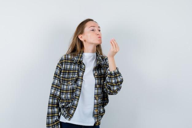 Ritratto di giovane donna che invia un bacio d'aria con le labbra imbronciate in t-shirt, giacca e carina vista frontale
