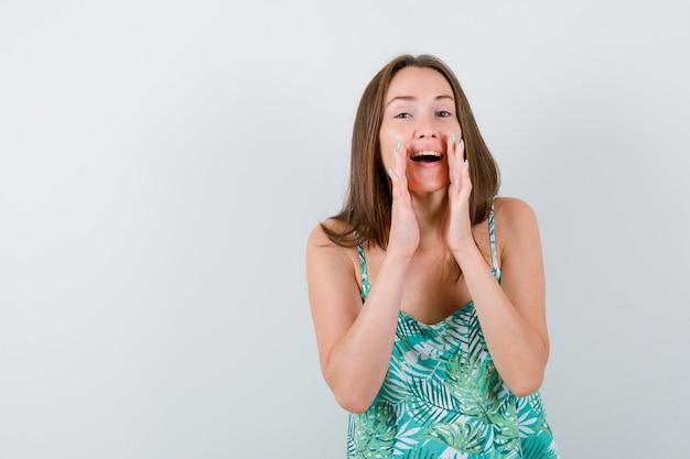 Ritratto di giovane donna che grida qualcosa con la mano in camicetta e sembra felice vista frontale