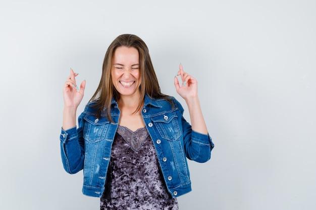 Ritratto di giovane donna che mostra le dita incrociate in camicetta, giacca di jeans e guardando la vista frontale allegra