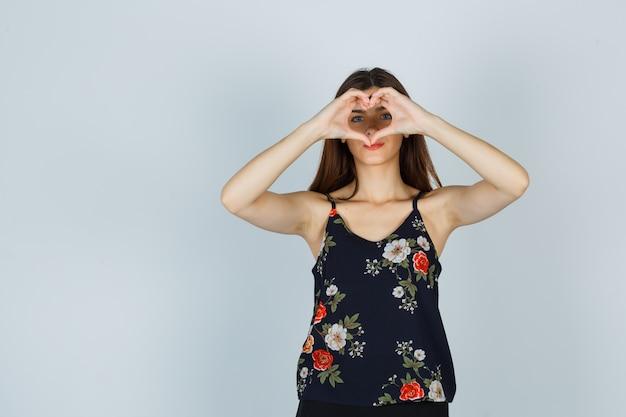 Ritratto di giovane donna che mostra il gesto del cuore in camicetta e sembra una vista frontale sicura