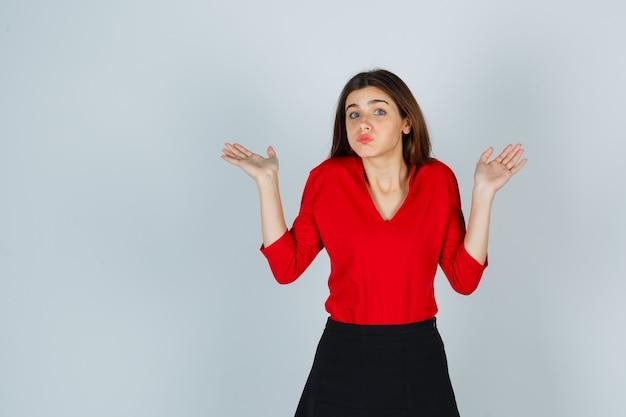 Ritratto di giovane donna che mostra gesto impotente in camicetta rossa