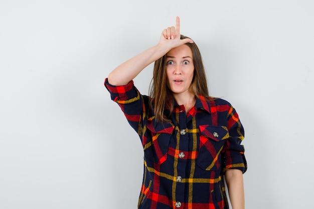 Ritratto di giovane donna che mostra il segno del perdente sulla fronte in camicia casual e guardando stupito vista frontale