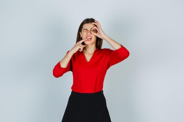 Ritratto di giovane donna che mostra il gesto giusto mentre morde il dito in camicetta rossa