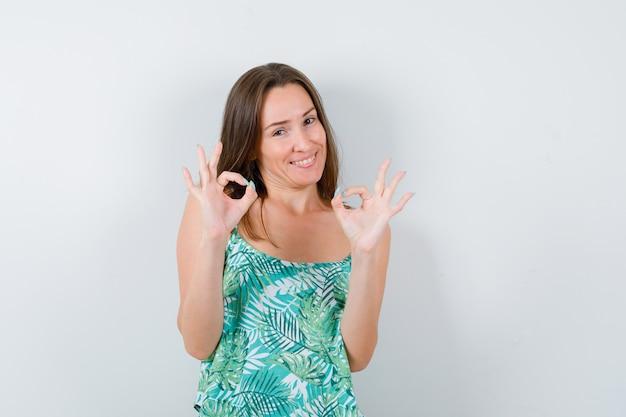 Ritratto di giovane donna che mostra il segno ok e sembra una vista frontale allegra