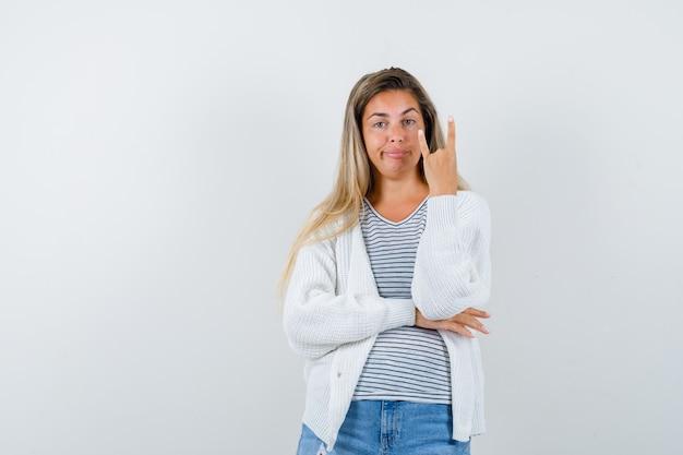 Ritratto di giovane donna che mostra gesto di roccia in t-shirt, giacca e guardando fiducioso vista frontale